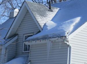 На кромке крыши, прямо над желобом хорошо видна ледяная дамба. обычно это - признак того, что через чердак интенсивно убегает тепло. Можно порою винить и окна, но в этом конкретном случае окон под дамбой нет. Такие дамбы могу оказаться опасны тем, что в определённый момент желоб не выдержит.